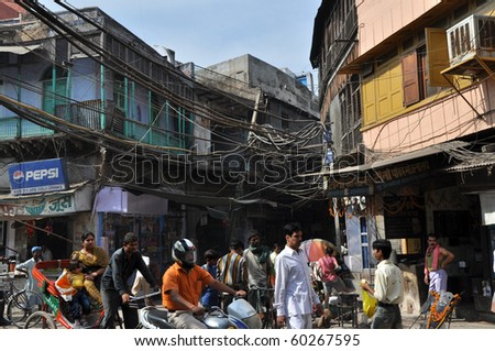 OLD DELHI, INDIA - OCTOBER 24: People travel under the risky and chaotic electrical wiring on October 24, 2009 in Old Delhi, India. Unsatisfying condition of wiring causes power problems in Delhi. - stock photo
