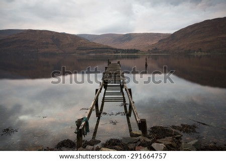 old derelict jetty in scotland overlooking mountains - stock photo