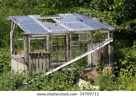 Old derelict shed in an overgrown allotment plot - stock photo