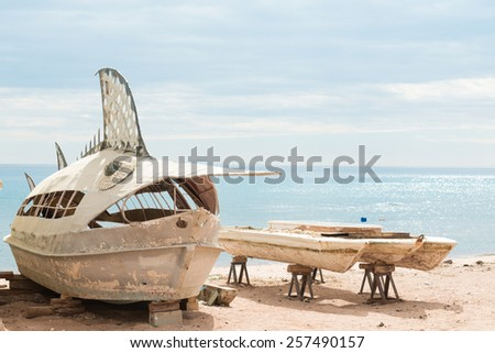 Old deserted fishing entertainment boats on the beach of Red Sea - stock photo