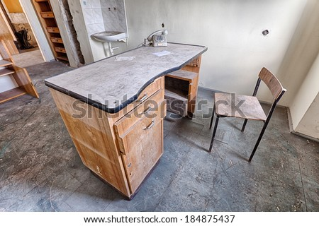 Old desk and chair in an abandoned hospital - stock photo