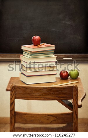 Old desk with a stack of books and apple with vintage look - stock photo