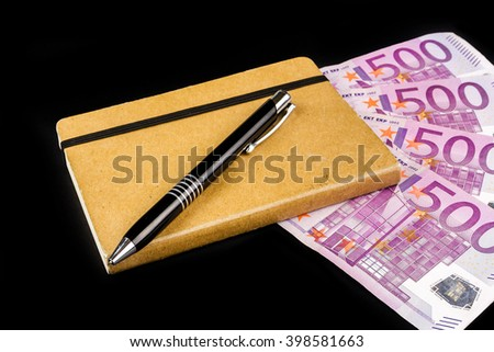 old diary with a pen and big euro banknotes on black background - stock photo