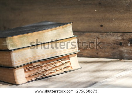 Old difference versions of holy bibles on wooden background - stock photo