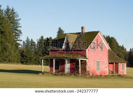 Old dilapidated house in a nicely moved grass field in the Fraser Valley of British Columbia. The roof covered in moss and windows and doors boarded up - stock photo
