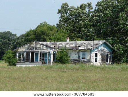 old dilapidated white house at edge of trees - stock photo