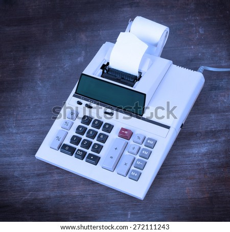 Old dirty calculator on a wooden desk - cold blue filter - stock photo
