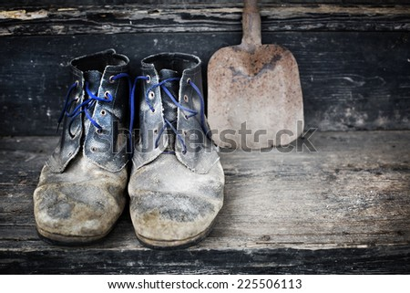 Old dirty cowboy boots/ Old and dirty military bootson wooden background - stock photo