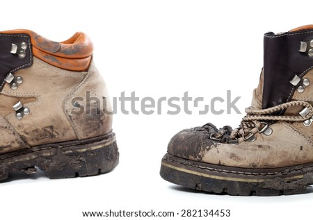 Old dirty hiking boots isolated on white background. Selective focus.  - stock photo