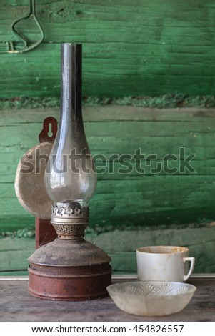 Old dirty kerosene lamp on a dusty table - stock photo