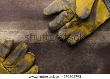 old dirty leather work gloves on wood background - stock photo