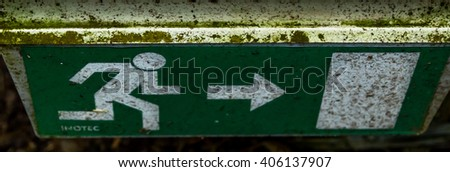 Old Dirty Weathered Emergency Exit Sign in Forest - stock photo