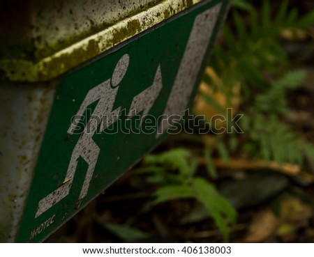 Old Dirty Weathered Emergency Exit Sign in Jungle - stock photo