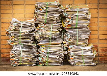 old document piles tied with plastic rope on brick background - stock photo