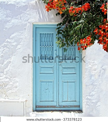 old door and white plastered wall on a greek Island in the sun - stock photo