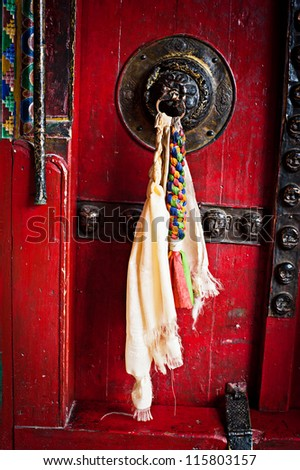 Old door at Buddhist monastery temple decorated with ancient doorknob and tassel. India, Ladakh, Diskit monastery - stock photo