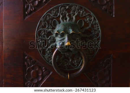 Old door handle made of statuary bronze - stock photo