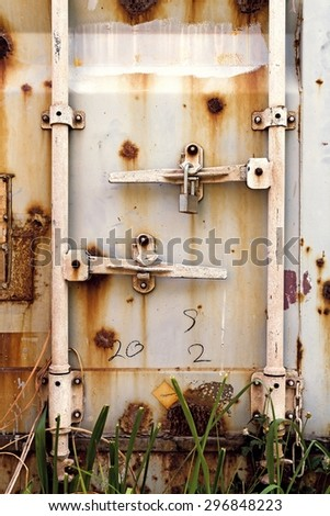 Old door of container on the ground with grasses.Used film filter for old tone. - stock photo