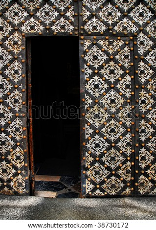 Old door with ornament in stone wall - stock photo