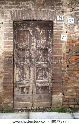 Old door with three different house numbers, Montebello della Battaglia, Italy. - stock photo