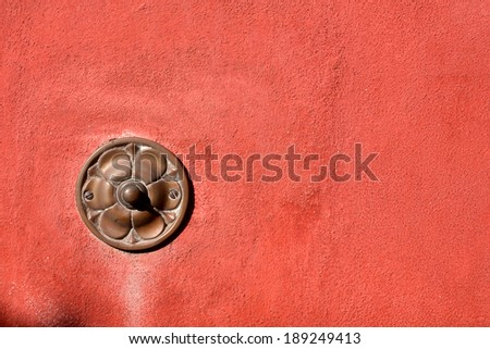Old Doorbell on Wall - Liguria Italy / Old brass doorbell button on red wall in Tellaro, ancient small village of Liguria in Italy - stock photo