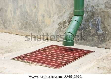 old drain pipe and rusty sieve of culvert at the side of building - stock photo