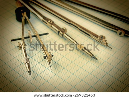 Old drawing tools on graph paper. Toned - stock photo