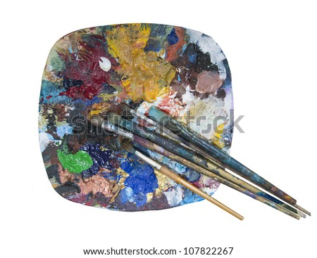 old dried paint and paint brushes on a plate being used as a mixing palette - stock photo
