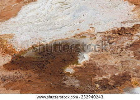Old dry white bacteria and mineral deposits above hot water filled shallow pools with colorful live bacteria as a background in Yellowstone National Park. - stock photo
