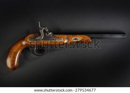 Old duel pistol on black background - stock photo