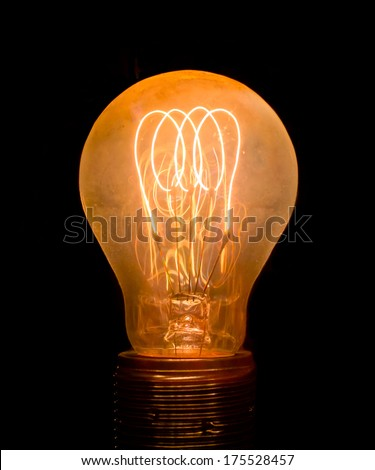 Old dusty light bulb  glowing in the dark - stock photo