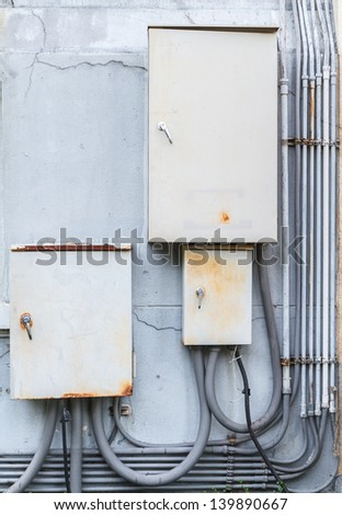 old electric boxs on wall - stock photo