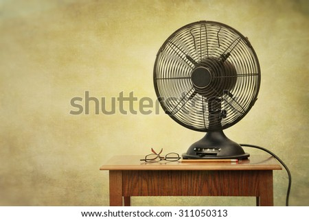 Old electric fan on table with retro look feeling - stock photo