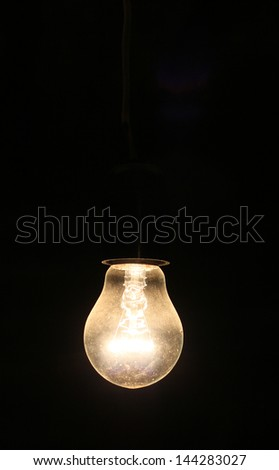 Old electric lightbulb in darkness - stock photo
