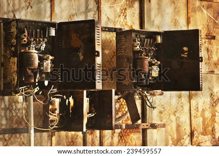 old electric meters, Aged electric switch boxes in front of old wall background - stock photo