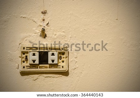 Old electric outlet in an old house interior on wall concrete - stock photo
