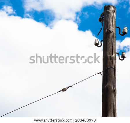 Old electric pillar falling apart on sky background - stock photo