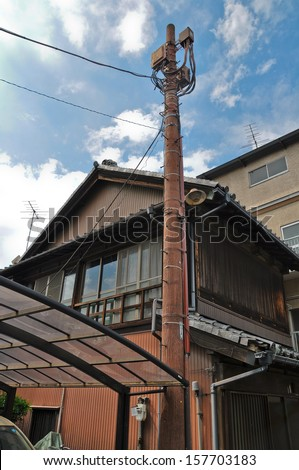 old electricity wood post with old japanese house - stock photo