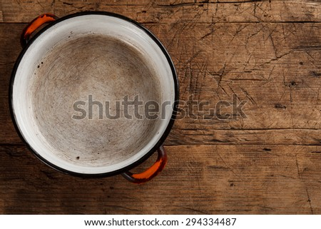 Old empty metal bowl on rustic wooden background - stock photo