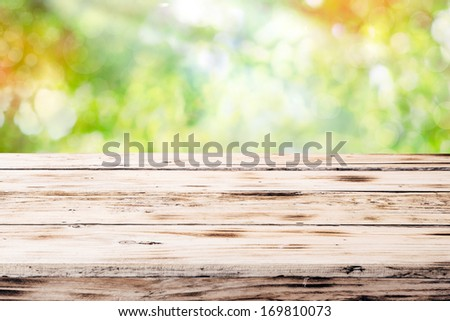 Old empty rustic grunge wooden table top against a blurred green blurred outdoor backgorund with copyspace - stock photo