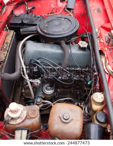 Old engine installed in red car - stock photo