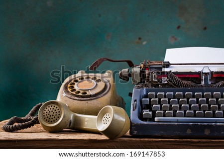 Old English type writer with paper sheet and telephone, still life - stock photo