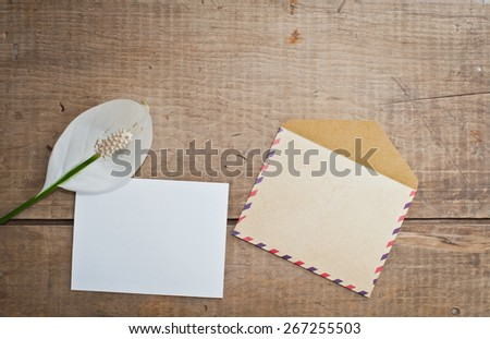 Old envelope and card with flower on wooden background - stock photo
