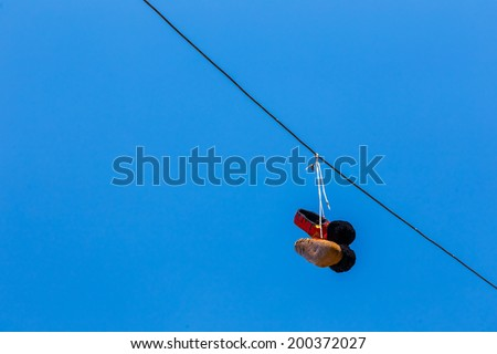 Old Euzone shoes thrown into the air and locked on telephone cable as a joke - stock photo
