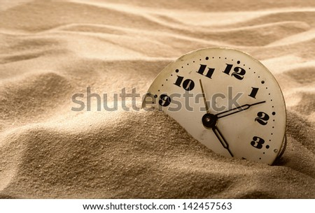 Old face of clock in sand - stock photo