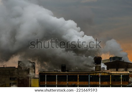 Old factory polluting the atmosphere with smoke and smog. - stock photo