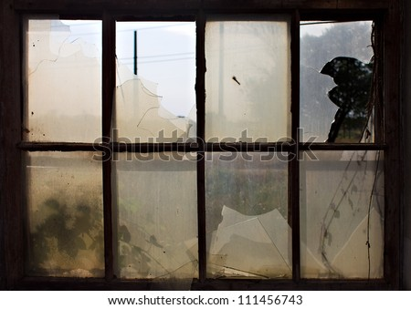 Old factory window with broken glass - stock photo