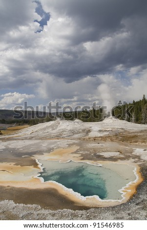 Old faithful area in Yellowstone national park. The vivid colors in the spring are the result of pigmented bacteria in the microbial mats that grow around the edges of the mineral-rich water. - stock photo