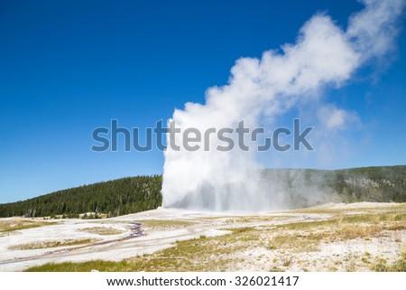 Old Faithful geyser eruption into Yellowstone National Park, USA - stock photo