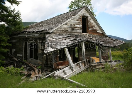 Old falling down house in the trees. - stock photo